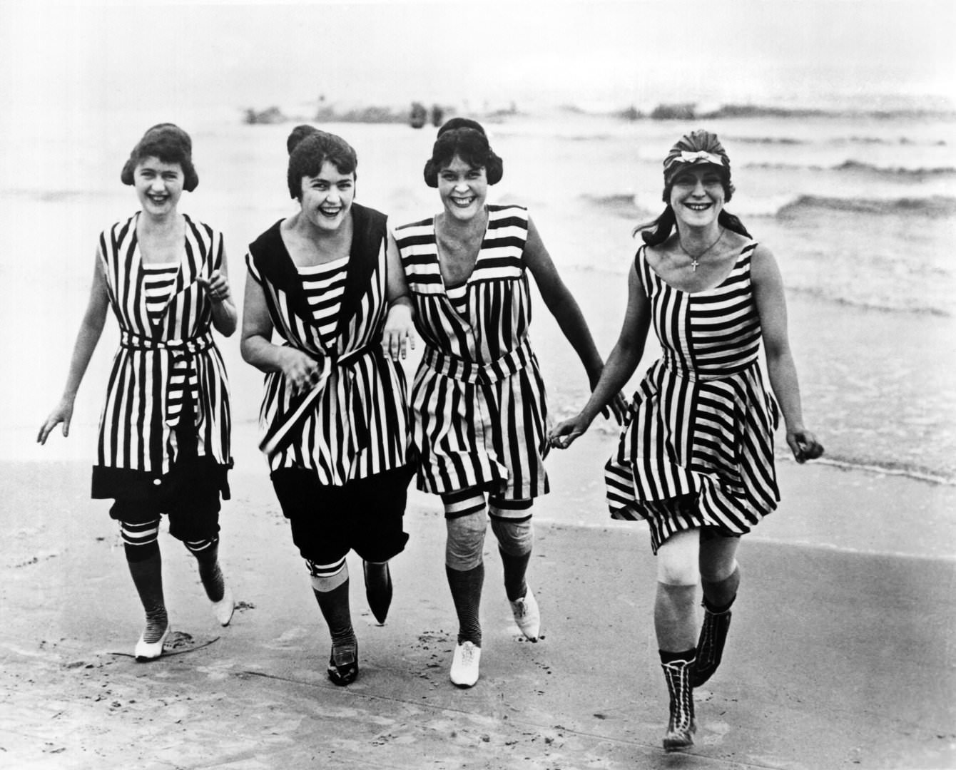 Four young women in matching beach wear run out of the surf, Los Angeles, 1910