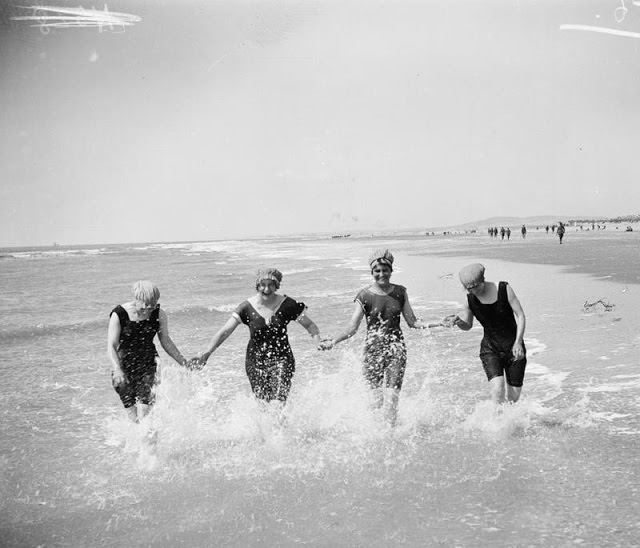 4 Women enjoying at beach with differnt bathing suits, 1912
