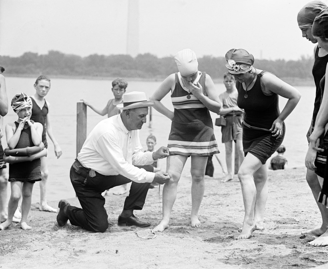 Woman having her swimsuit measured for length violations on a Washington DC beach, 1922