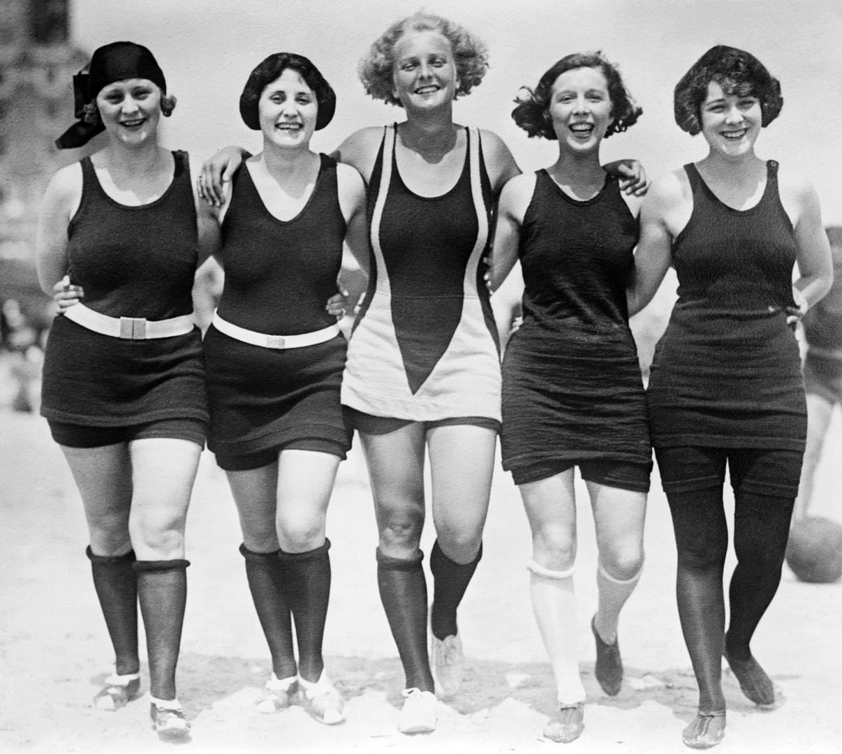 Five women walking arm-in-arm on the beach wearing wool bathing suits, 1925