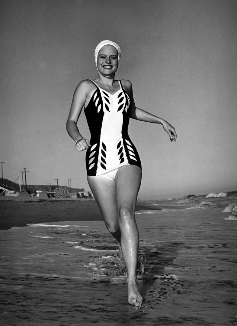 Actress Alexis Smith in a swimming costume running along the beach in southern California, 1940