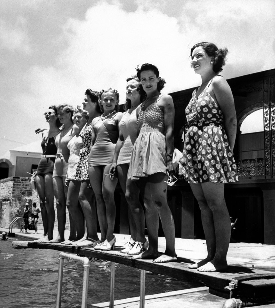 Bathing suit clad female members of the British Imperial Censorship Staff,standing poolside at the Princess Hotel, 1941