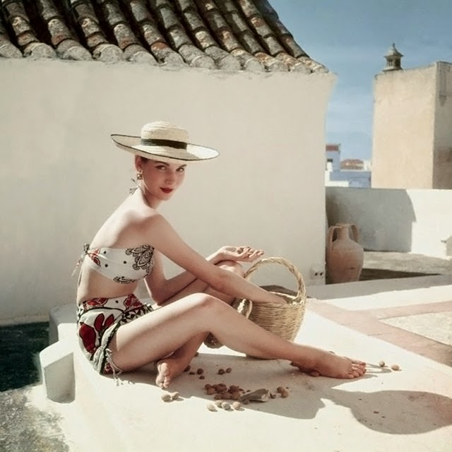 Model seated with basket on a rooftop, wearing Calypso designed patterned bikini, 1952