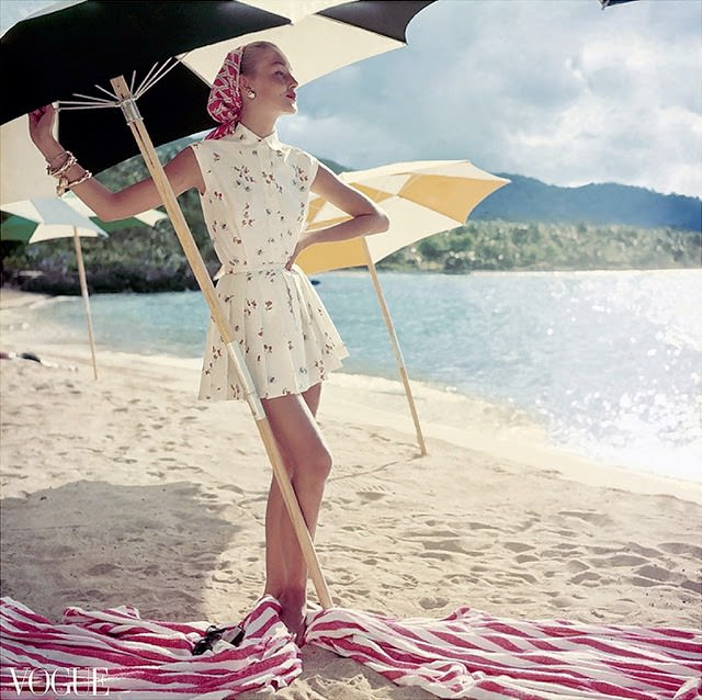Model standing under beach umbrella wearing summer dress look; pleated short shorts and matching sleeveless shirt, both in a light floral pattern. 1954