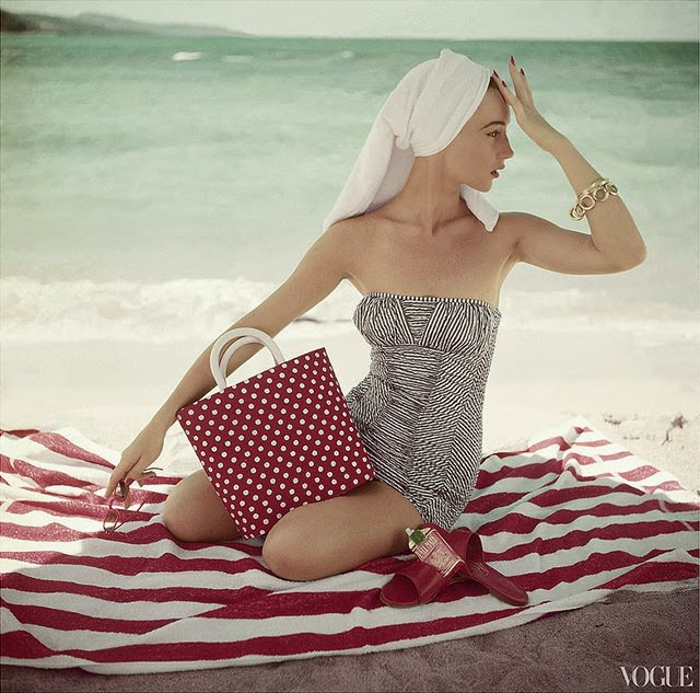 Model seated on striped beach towel wearing grey and white patterned strapless bathing suit, 1954