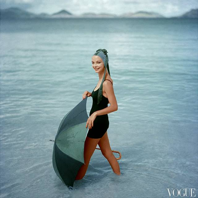 Gretchen Harris, standing in ocean with open green and blue umbrella, wearing knitted black maiilot of DuPont and water-velvet cap , 1957