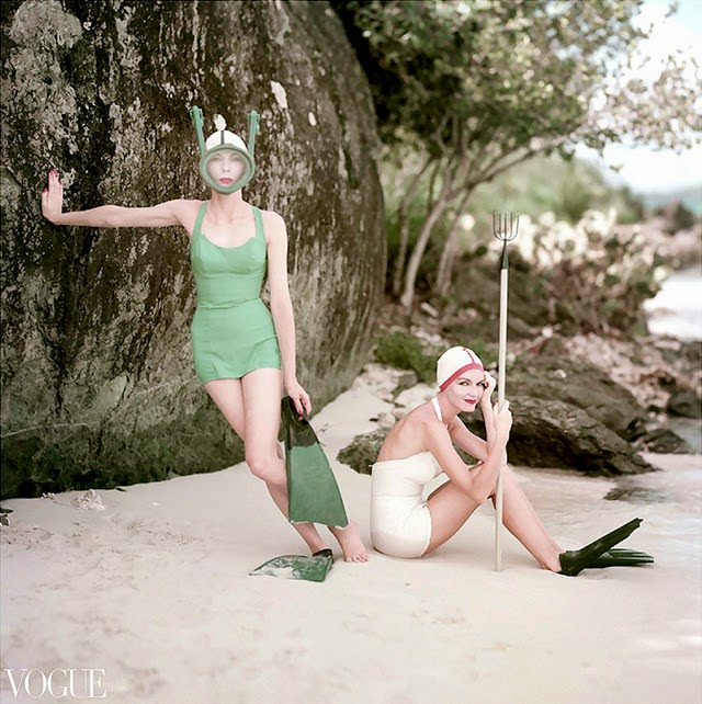 Two models in Rose Marie Reid swimsuits. Model on left stands tree wearing blue suit, mask and flippers; model on right wears white suit with matching cap, and flip