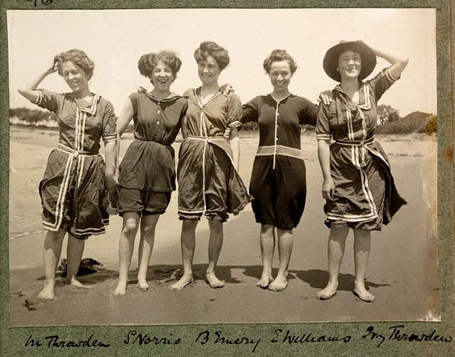 Women wearing 1900s swimsuits having right down to the collars and buttons made from heavy flannel or wool fabrics