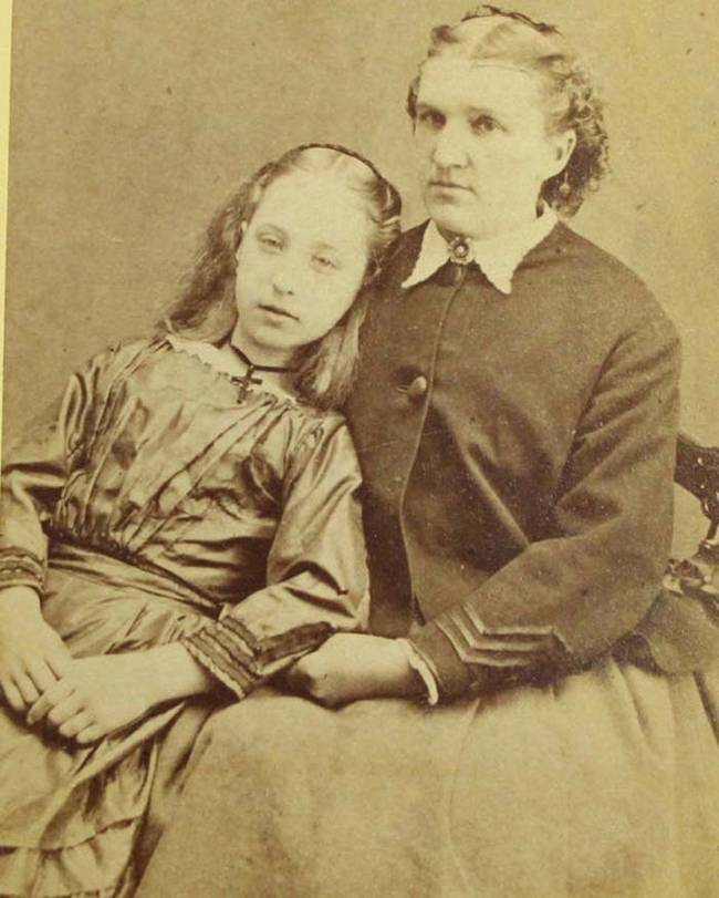 Women sitting next to dead girl. These death portrait were meant to serve as mementos of the deceased loved one.