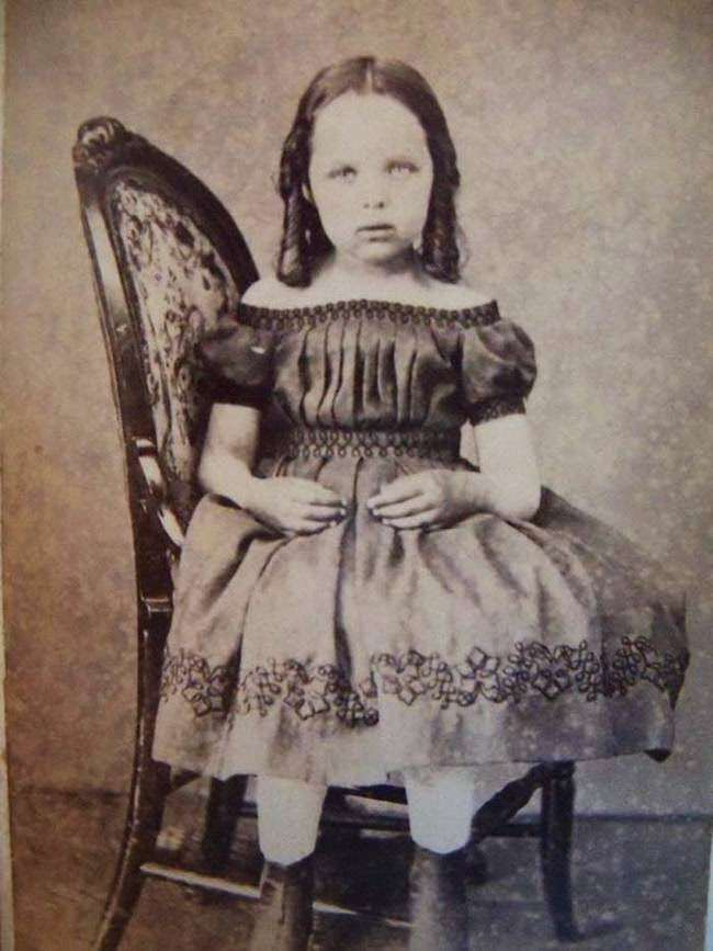 Little girl sitting sideways on the chair, the device propping her up is hidden.