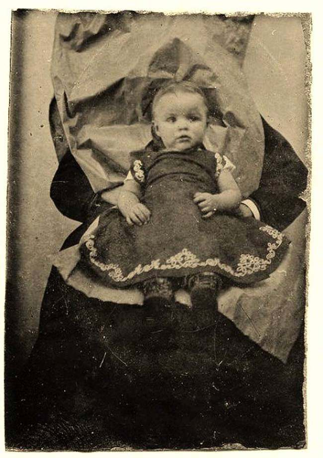 A little girl sitting on someone's lap. The person held her in place while the photo was taken.