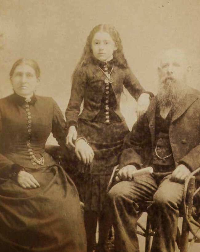 The girl standing in the middle is the deceased.The photographer attempted to make her look more alive by drawing on her pupils.