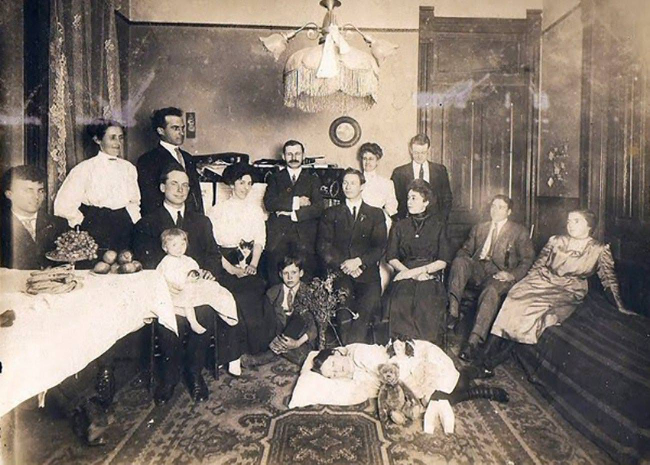 Dead girl is  is lying on the floor of the parlor surrounded by family members.