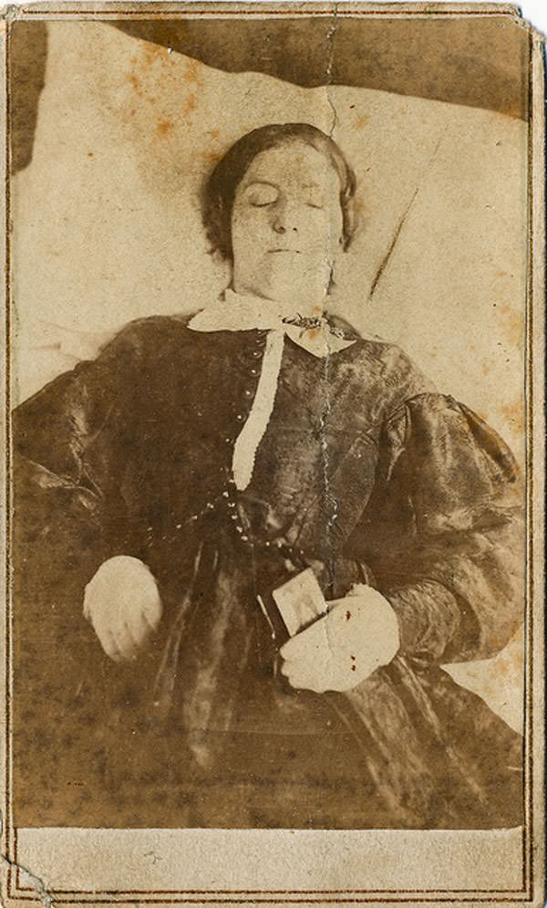 Deceased young woman is holding a small bible or testament.