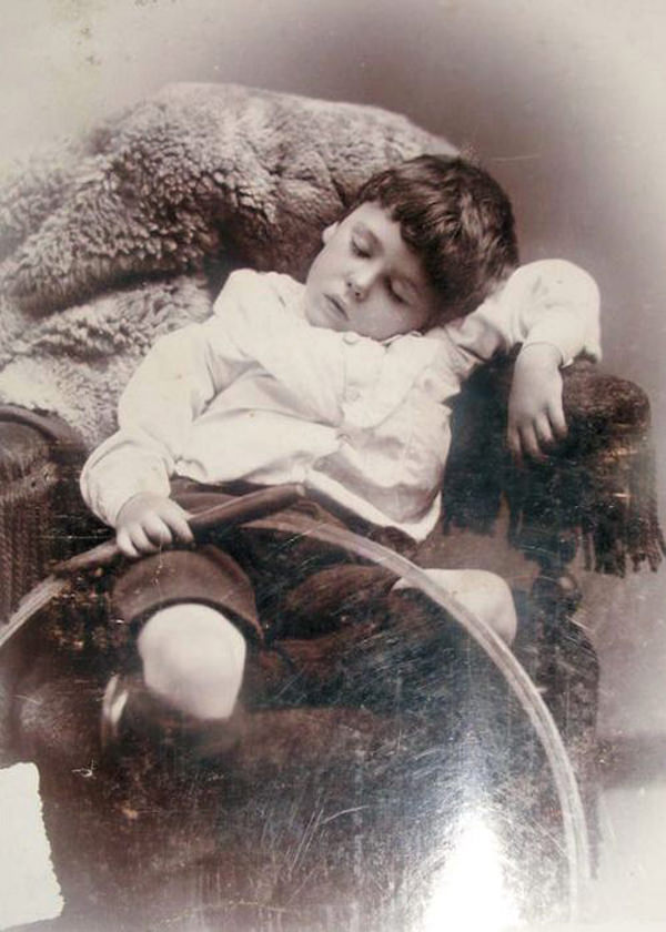 Deceased boy photographed with what was likely his favorite toy, a hoop and stick.