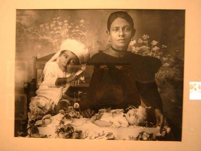 Mother and older sibling posing over a deceased infant.
