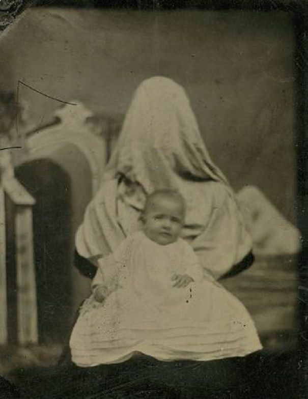 A mother covers her face while holding her dead baby.