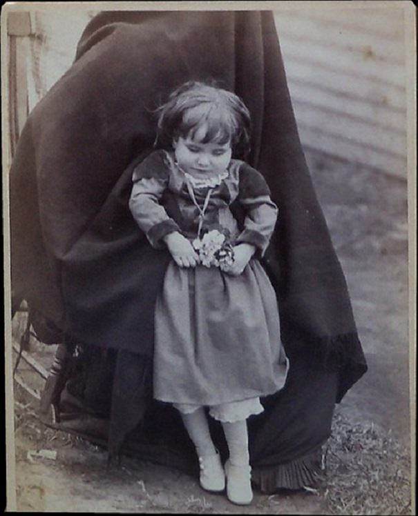 Little girl held in a standing position. The photo is a cabinet card from Villisca, Iowa taken in 1890.