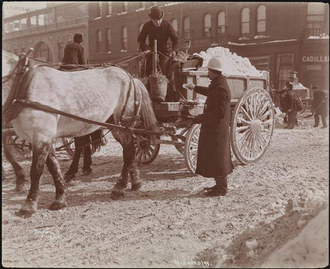 A police officer handing something to a horse-cart driver hauling snow, 1899