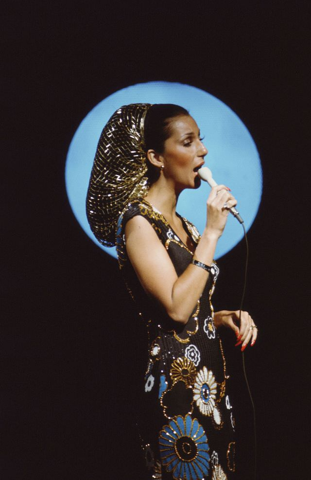 Promotional portrait of Cher as she sings into a microphone for the television variety show 'The Sonny and Cher Comedy Hour, 1972