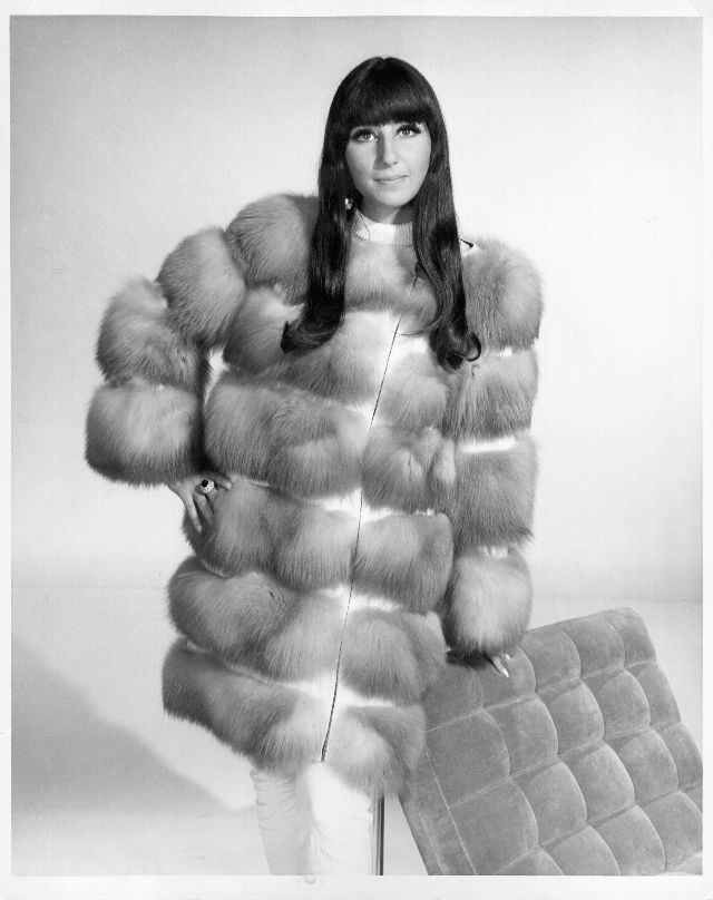 Cher poses for a portrait wearing a fur coat. Photo by Michael Ochs Archives, 1966