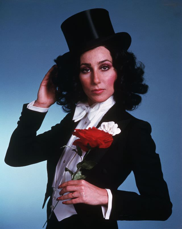 Cher, wearing a tuxedo and top hat, holds a red rose. Photo by Bettmann, 1975
