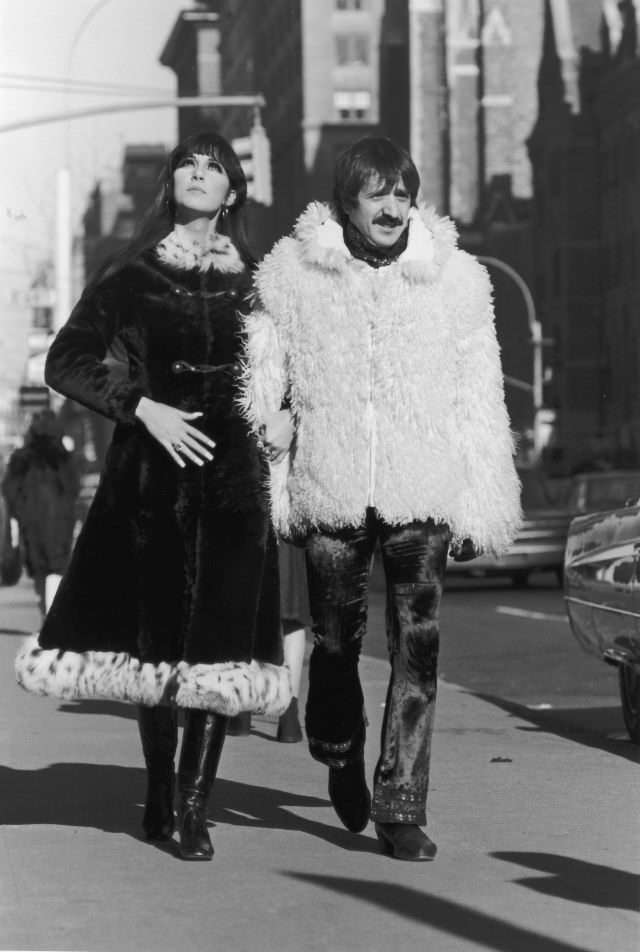 Sonny Bono, in a Mongolian lamb's wool jacket, and Cher, in a long fur overcoat trimmed with leopard fur, walk arm-in-arm down the sidewalk, New York City. Photo by Jack Robinson.
