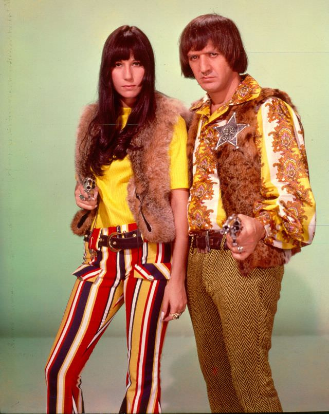 Sonny Bono and Cher point guns toward the camera as they pose for a portrait. Photo by Michael Ochs Archives, 1970