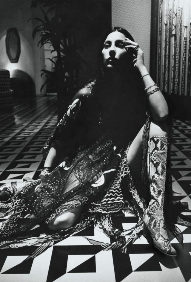 Cher wearing snakeskin boots and a chiffon dress by Zandra Rhodes. Photo by Charles Tracy for Vogue, 1970