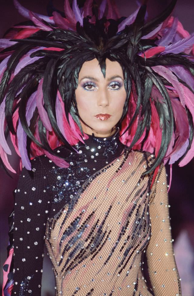 Promotional portrait of Cher in a semi-transparent outfit with a feathered headdress for the television variety show 'The Sonny and Cher Comedy Hour, 1972