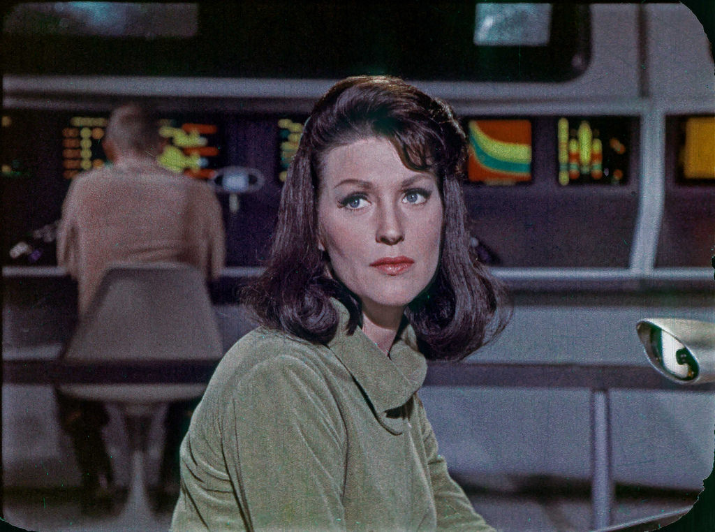 Majel Barrett in her original role from the Star Trek TOS pilot The Cage, as Number One, shown on the original bridge set of the Enterprise.