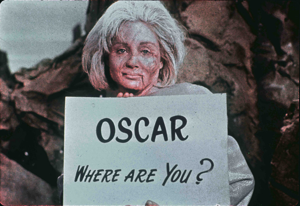 An historic and previously rarely seen shot of Susan Oliver in fully deformed state makeup and costume holding a sign with an inside joke directed towards Desilu executive Oscar Katz.