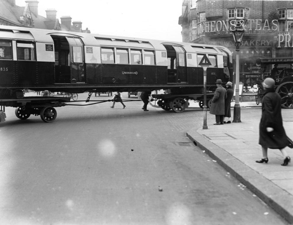 An underground train being transported on wheels through the streets of London, 1926.