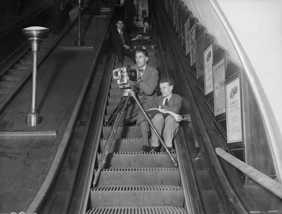 British director Anthony Asquith (1902-1968), right, directing his new film 'Underground' from an escalator on the London underground, May 1928.
