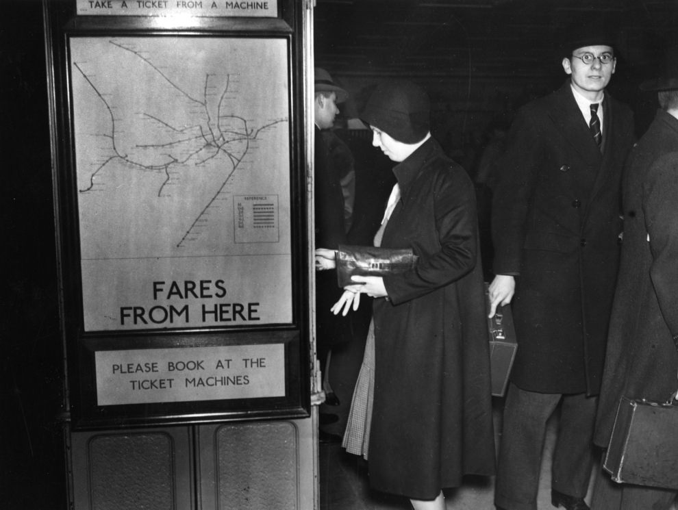 A passenger takes a ticket from the machine at Piccadilly Circus, 1930.