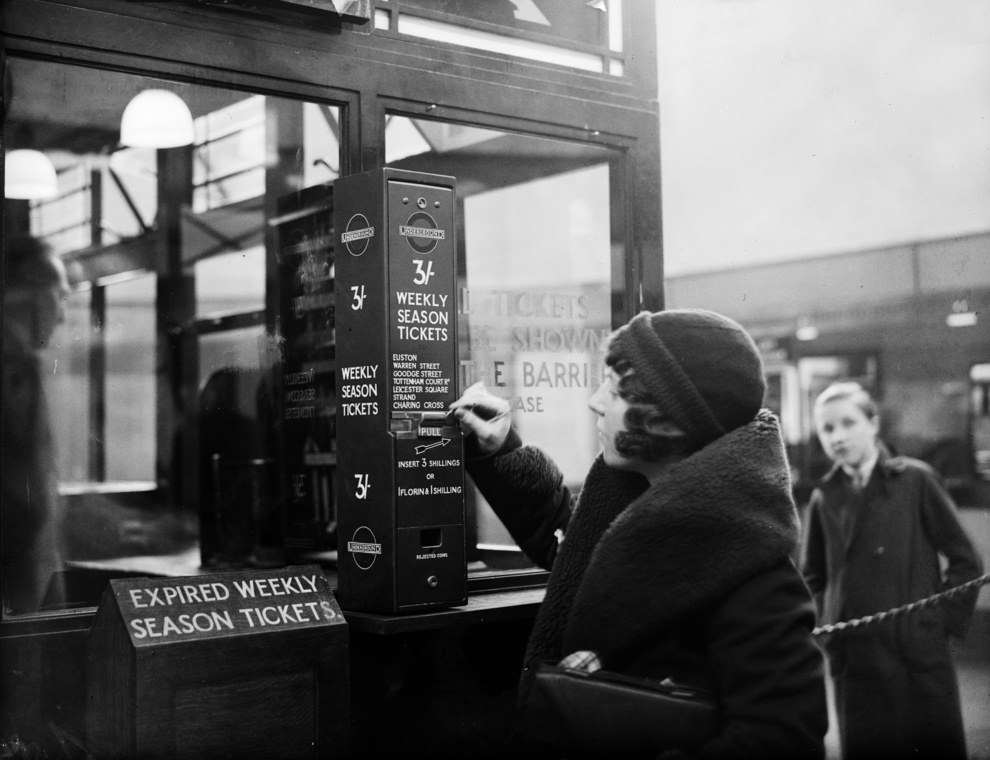 A traveller buys a London Underground season ticket from a vending machine at Highgate Station, 1932.