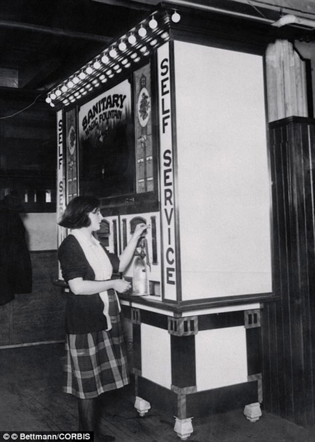 A woman uses The Maiwarm Company soda machine in 1928. It was the first of its kind not to require a soda squirter.