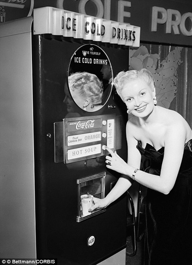 A woman demonstrates a multi functional vending machine that dispenses both cold drinks including Coca Cola, Canada Dry and orange juice along with hot soup, ca. 1950s.