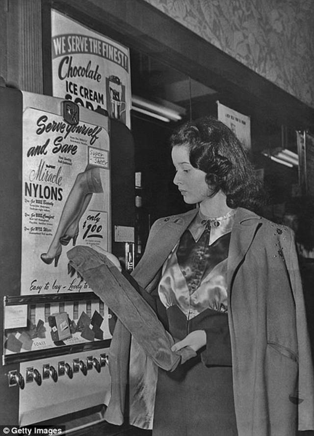 A woman also purchases a pair of nylon stockings from a machine, ca. 1950s.