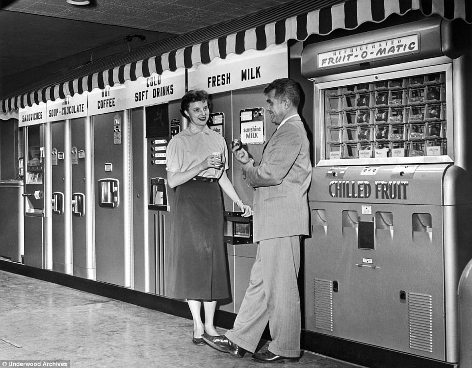 The market for vending machines was beginning to expand. This couple have a choice of sandwiches, hot soup or hot chocolate, coffee, cold drinks, fresh milk and chilled fruit from a series of automated vendors - arranged under a natty striped awning, 1959.