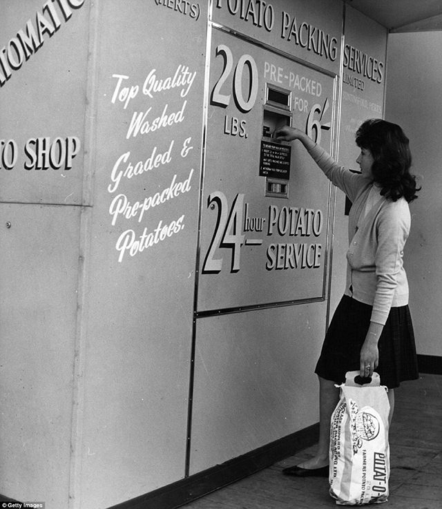 A woman is operating the first potato vending machine in Britain in Chelsea, 1962.