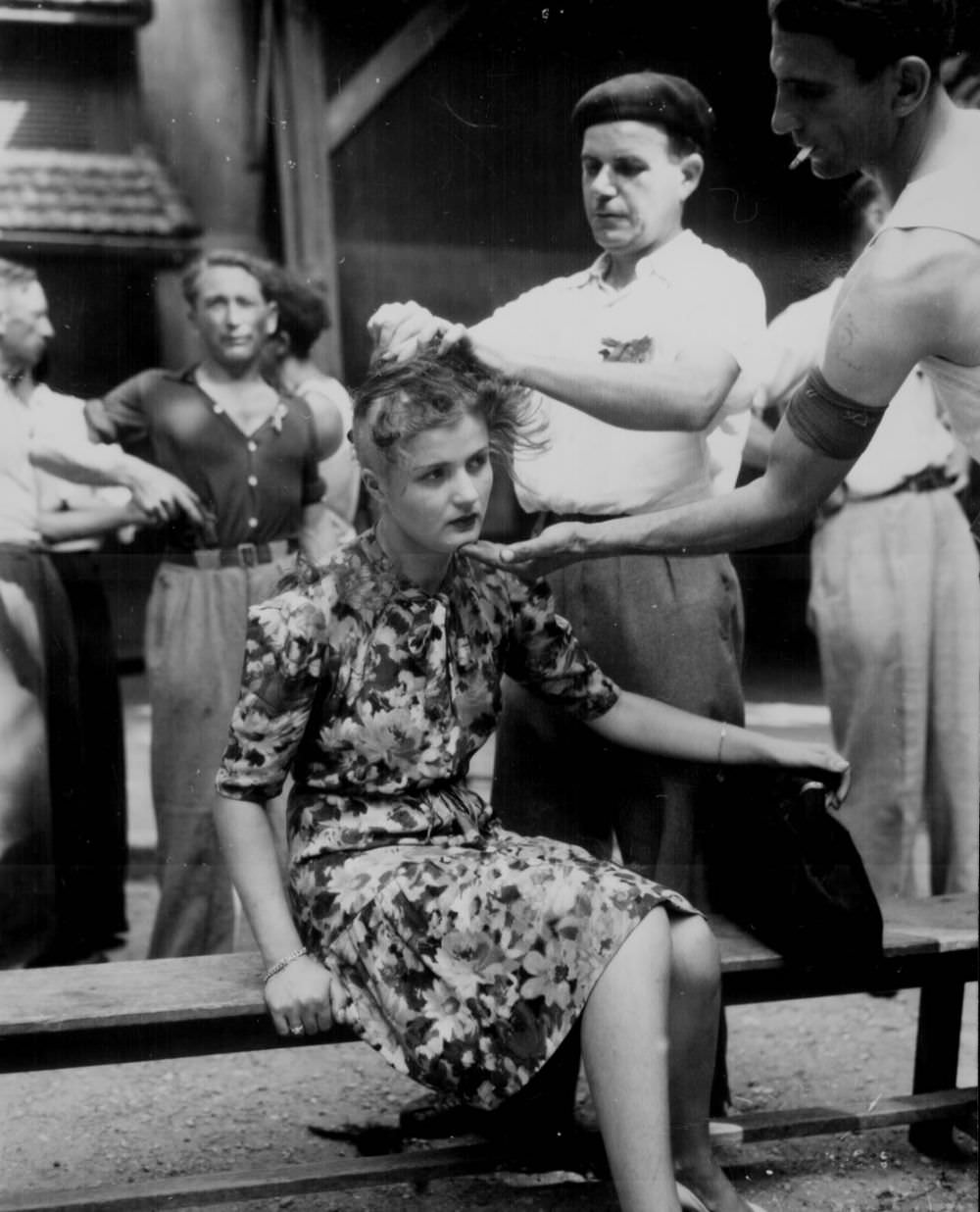 French female collaborator punished by having her head shaved to publicly mark her, 1944.