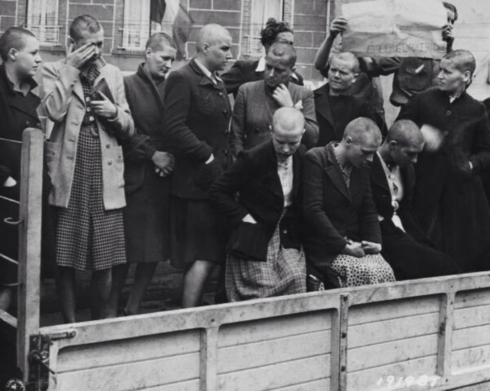 Brutalized women, their heads shaved, are loaded into the back of a truck. The 'man' behind them is holding a sign that says 'collaborators', but who is the real collaborator?