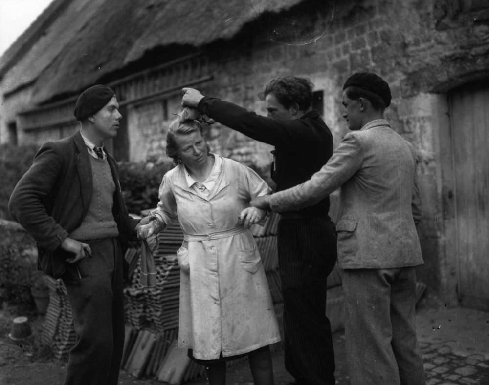 Two French patriots restrain a woman while another crops her hair after she has been accused of collaborating with the Germans during the occupation. January 01, 1945.
