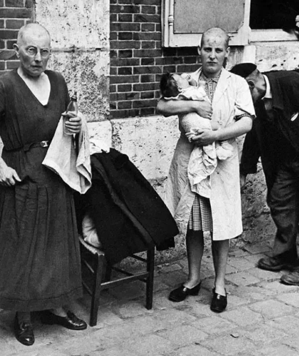 A Frenchwoman collaborator and her baby with her mother followed by a throng of taunting townspeople in August 1944.