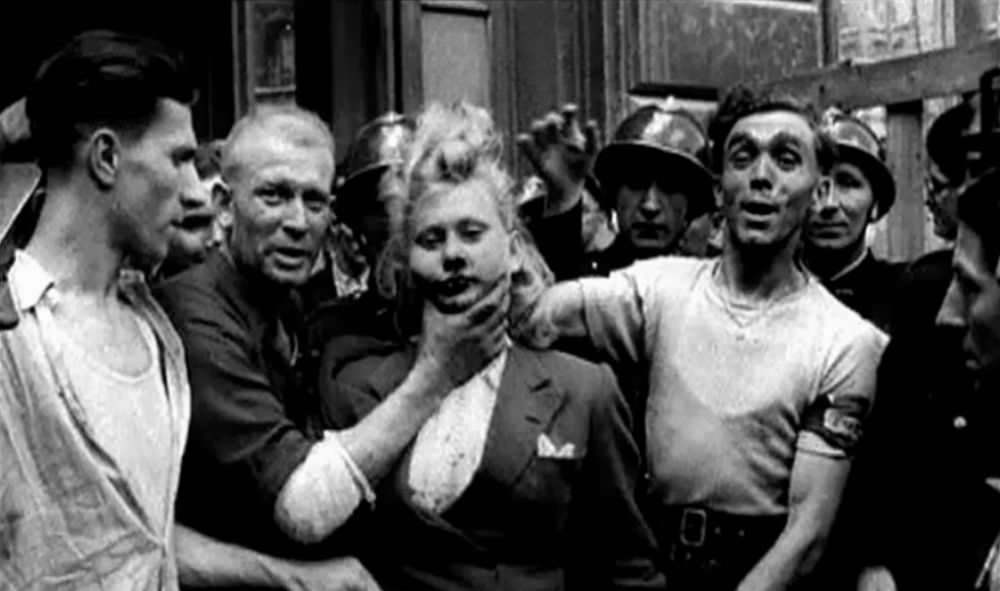 A French woman with a bloody face is forced to look at the camera while French soldiers do nothing.
