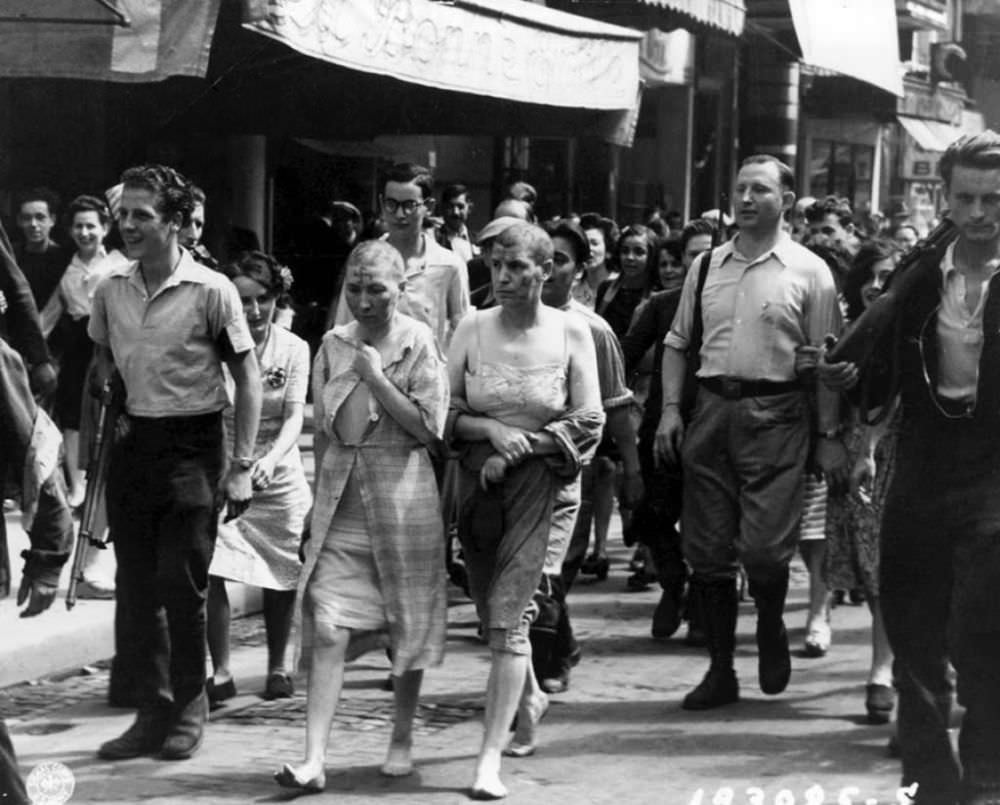Two women, partially stripped, their heads shaved and with swastikas painted on their faces, are marched barefoot down the streets of Paris, to shame and humiliate them for collaborating with the Germans during the Second World War. August 27, 1944.
