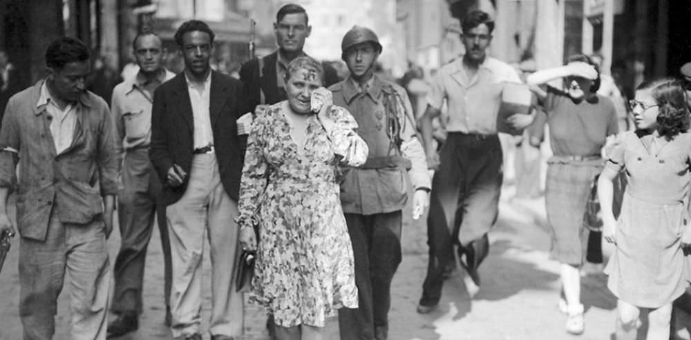 A sobbing French woman with a swastika smeared on her face is paraded through the streets with civilians and a soldier.