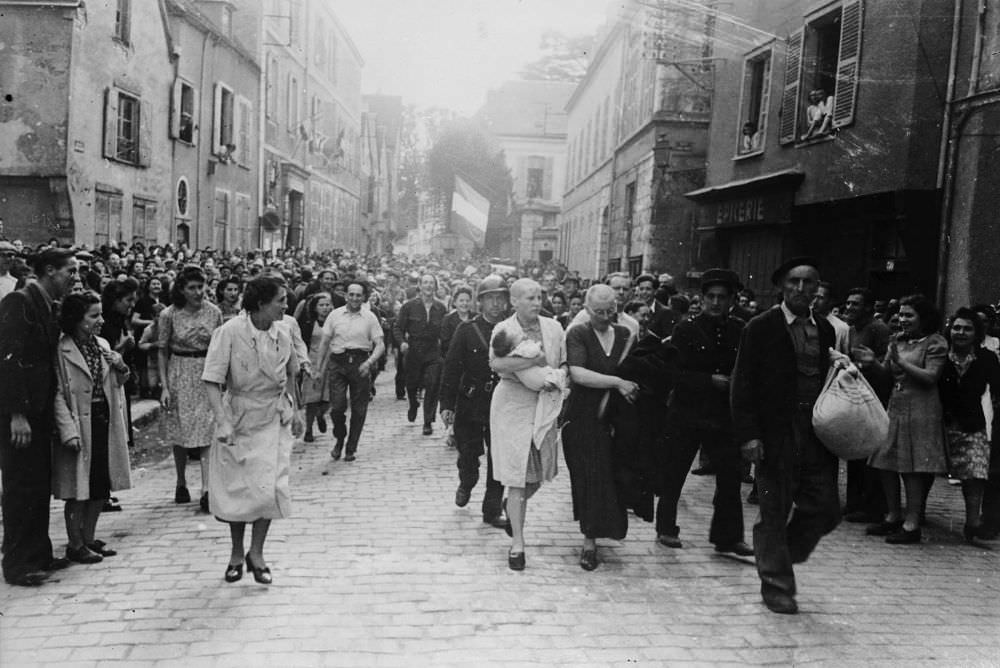 A woman, with her baby whose father is German, and her mother are jeered and humiliated by crowds in Chartres after having their heads shaved as punishment for collaborating with the German troops, 1944.