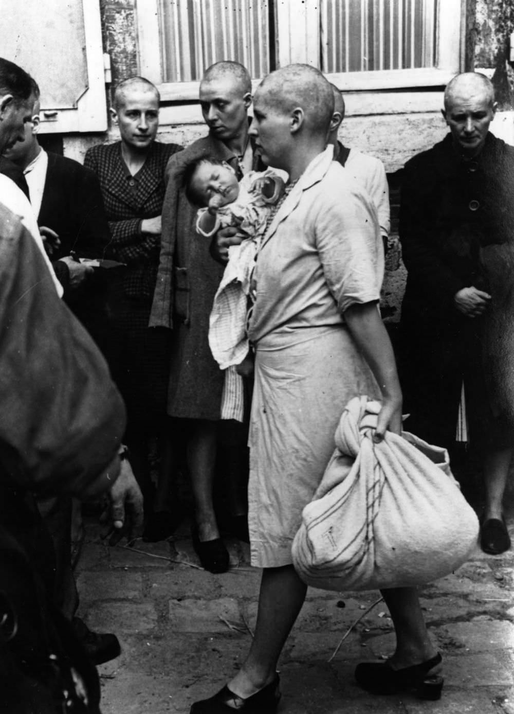 A French woman collaborator and her baby, whose father is German, tries to return to her home followed by a throng of taunting townspeople after having her head shaven following the capture of Chartres by the Allies, August 1944. It appears that she is passing some women who suffered a similar fate.